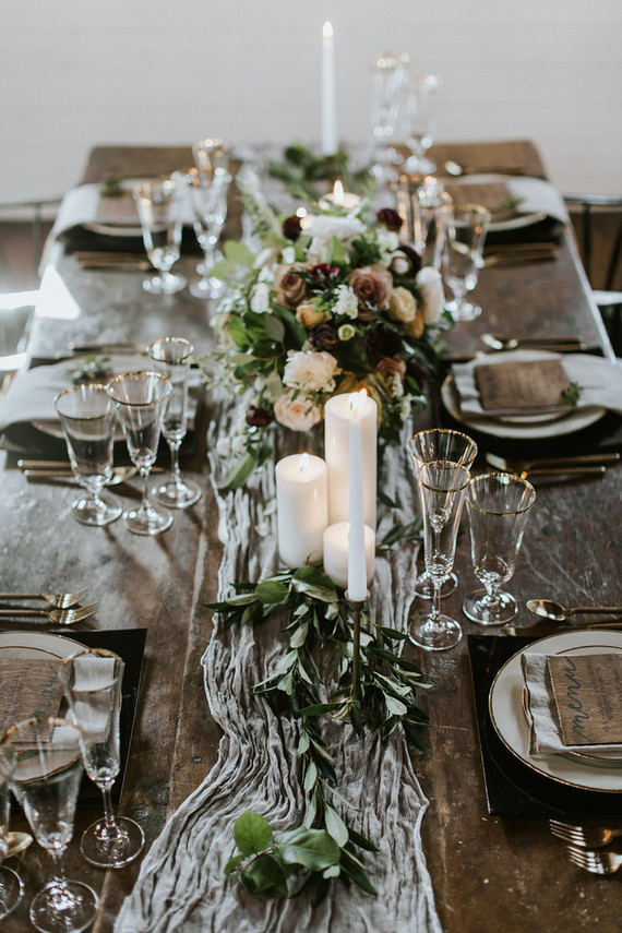 A rough wooden table, an ethereal table runner, gold rimmer glasses and a moody centerpiece played well together