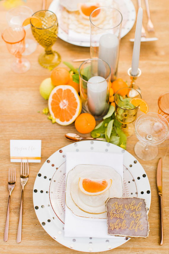 The tablescape was done with candles and different types of citrus, polka dot plates, quartz slice place cards