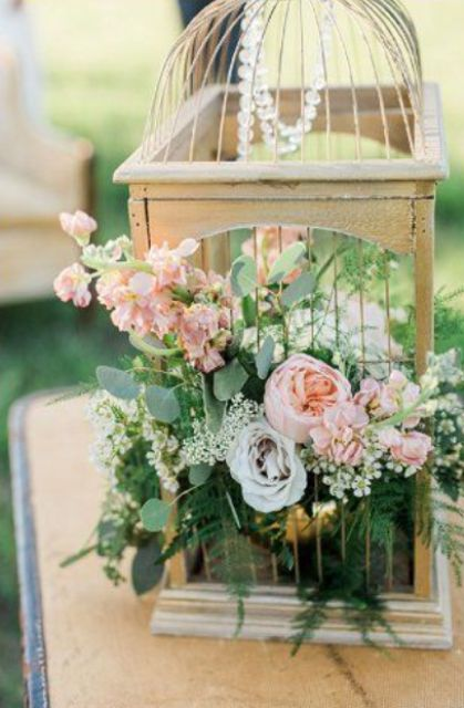 a birdcage with crystals, lush greenery and pink blooms for a garden wedding