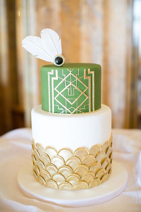 a wedding cake with gold scallops, a green layer with gold geo decor and edible feathers