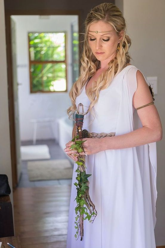 the bride dressed in elvish style, with a flowing gown, an arm band, a headpiece with a stone and a unique wedding bouquet