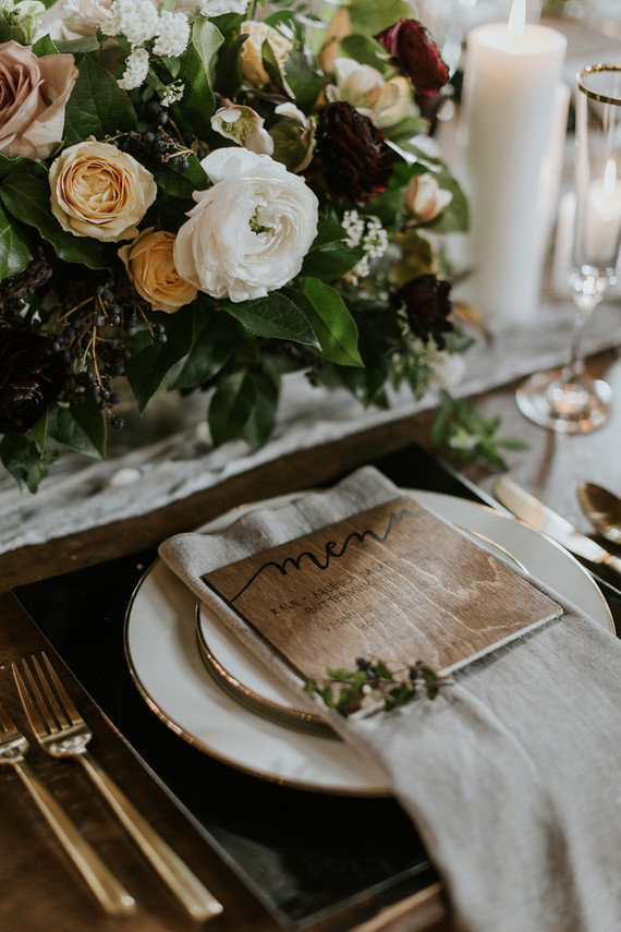 Black chargers, wooden menus, gold cutlery added interet to the tablescape