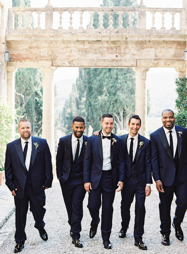 The groom was rocking a navy tuxedo with black details, and his groomsmen were wearing the same suits but three-piece ones with ties
