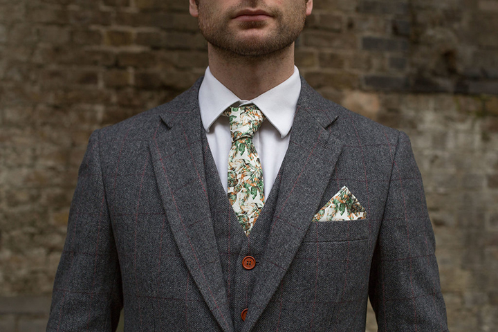 The groom was wearing a stylish grey suit with thin pink stripes, and a handcrafted tie with a botanical print