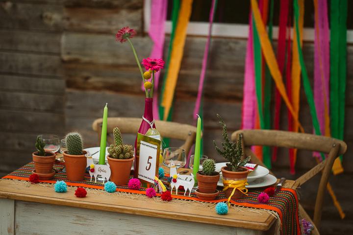 Hochzeit Tisch war dekoriert mit einer Peruanischen inspirierten Tischläufer, Pompons, eine mutige Flasche als vase und Kakteen