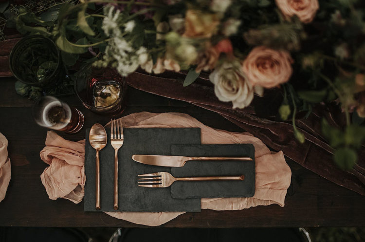You can see granite plates, rose gold cutlery and a plum-colored velvet table runner