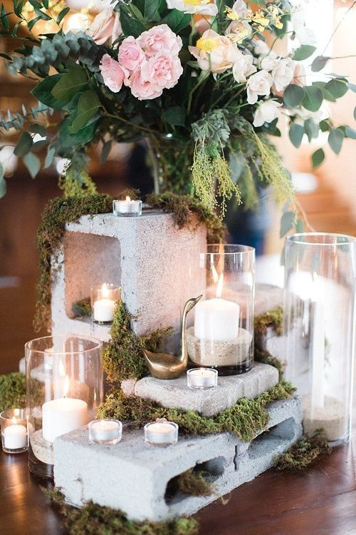 a concrete combo with moss and small candles, a lush flower centerpiece next to it