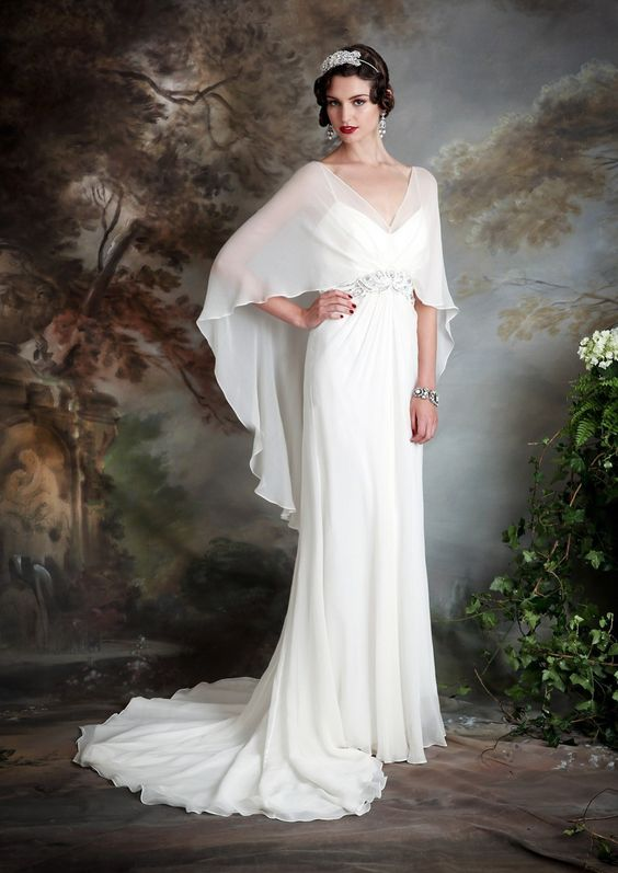 a spaghetti strap wedding dress with a sheer cape on top to cover up for a church ceremony