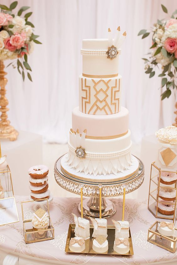 a white and gold wedding cake with geo decor, petals, beads, feathers and vintage brooches