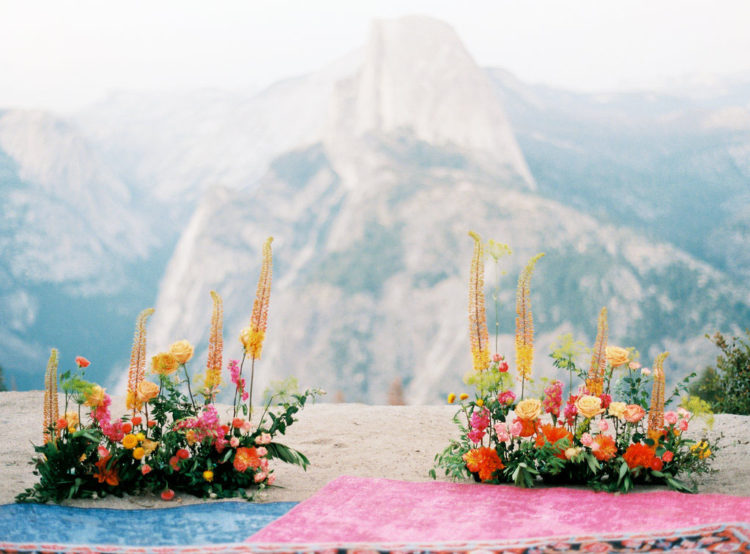 The ceremony space is decorated with orange, yellow, pink and red blooms and boho rugs