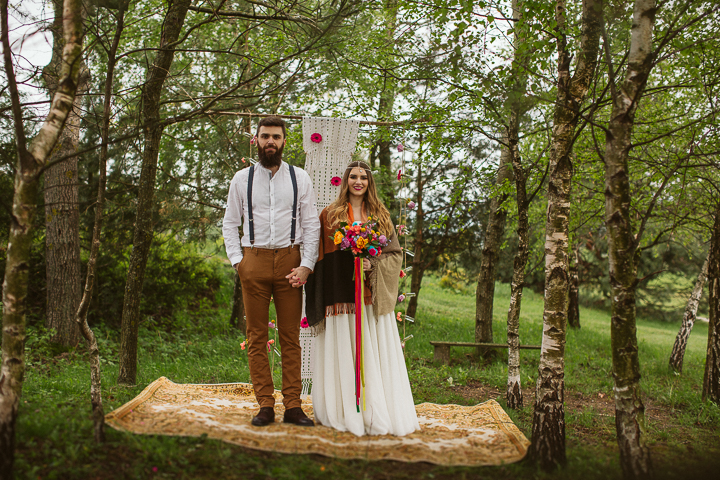 The ceremony space was right in the woods, there was a simple branch arch with lace and some bold blooms