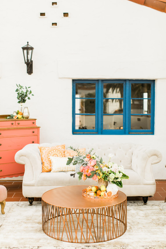 The wedding lounge was created with a white sofa, a copper table, citrus and bold blooms