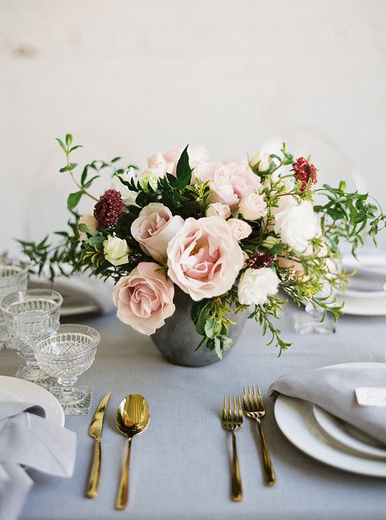 a concrete vase with lush blush flowers, greenery and burgundy touches