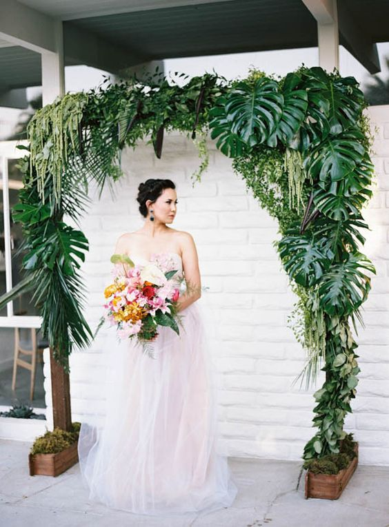 a wedding arch decorated with tropical leaves and hanging greenery and foliage