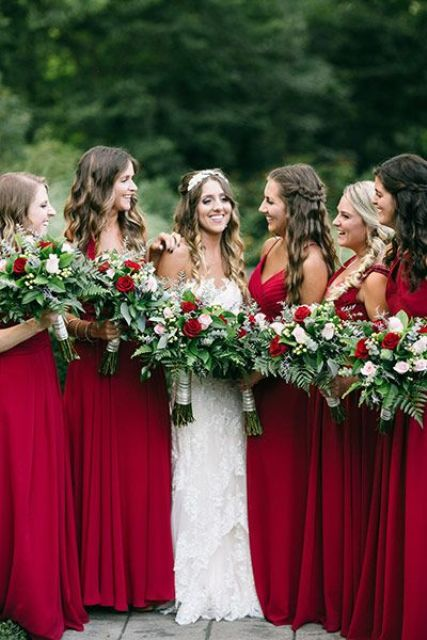 bridesmaids in chic red maxi dresses with textural greenery and red rose bouquets
