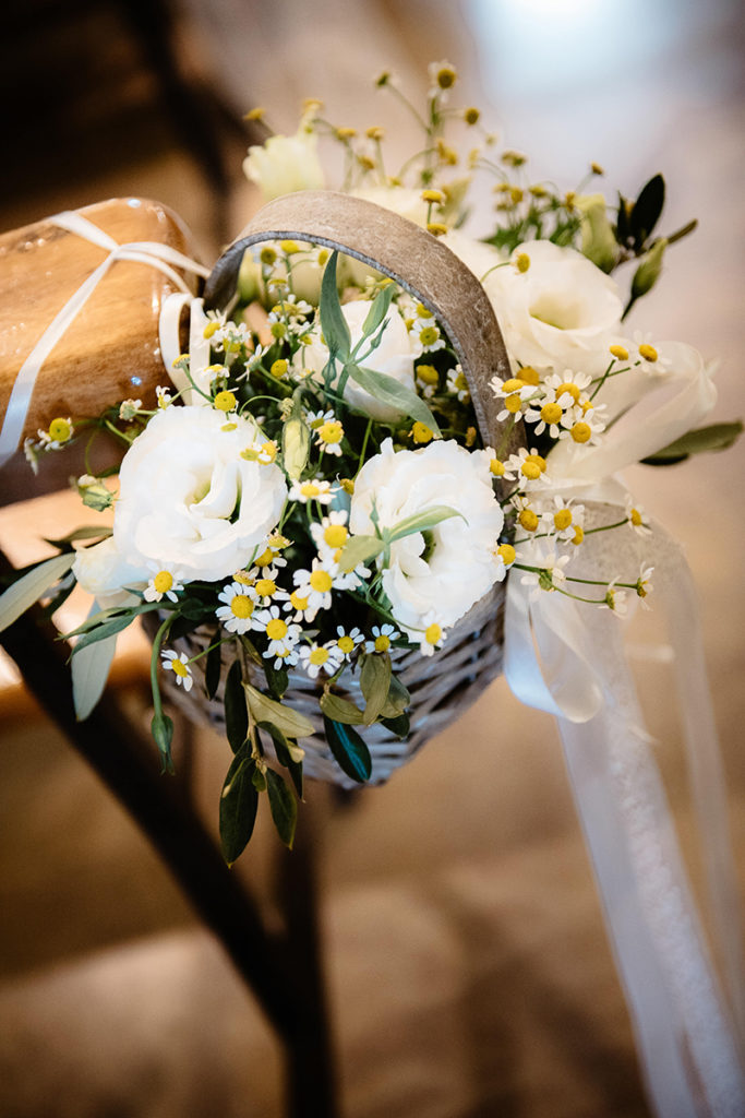 Neutral florals in baskets were used for aisle decor