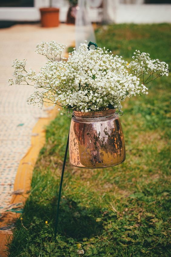 a copper kettle with baby's breath for lining up the aisle