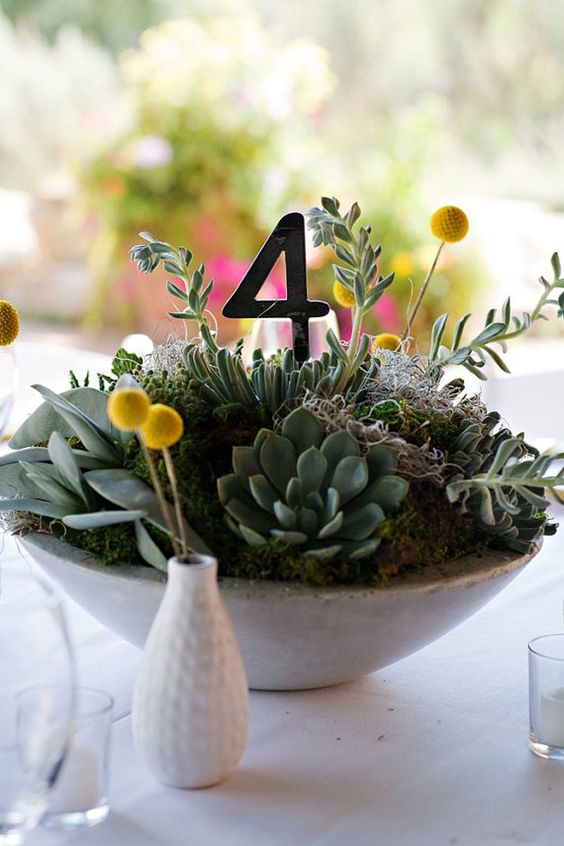 a large concrete bowl with moss, succulents, billy balls, a table number for a chic centerpiece