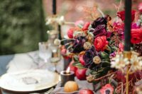 06 a refined moody wedidng tablescape with dark florals, pomegranates and gilded chargers