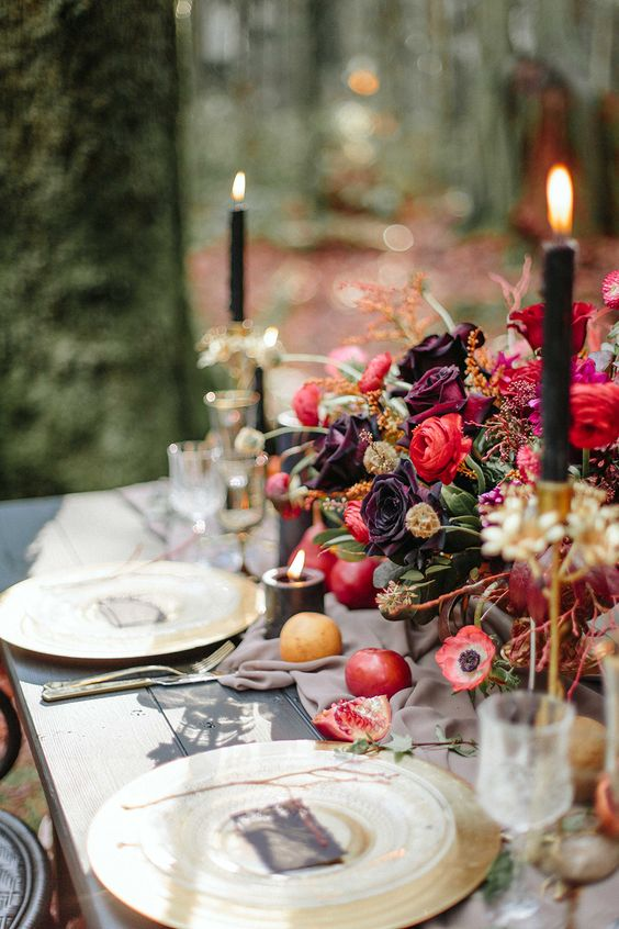 a refined moody wedidng tablescape with dark florals, pomegranates and gilded chargers