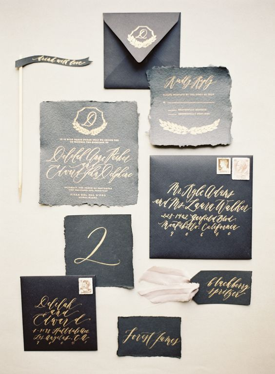 black textural wedding stationery with gold calligraphy and a raw edge
