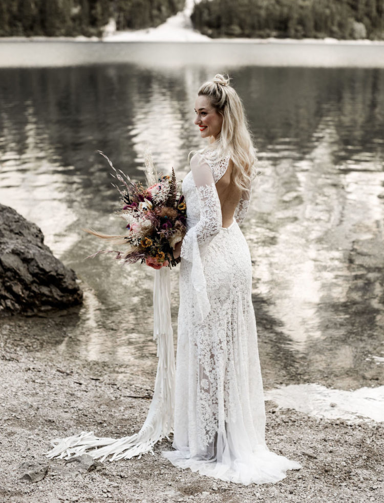 The boho lace wedding dress with wide sleeves and an open back looked very cool and the bouquet had ribbon that reminded of the dress