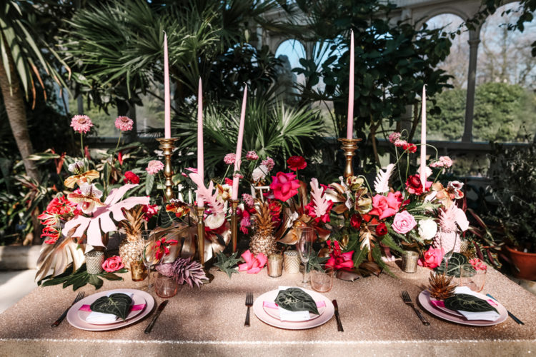 The bold tablescape was done with pink hues, gilded pineapples and tropical leaves, pink candles added glam