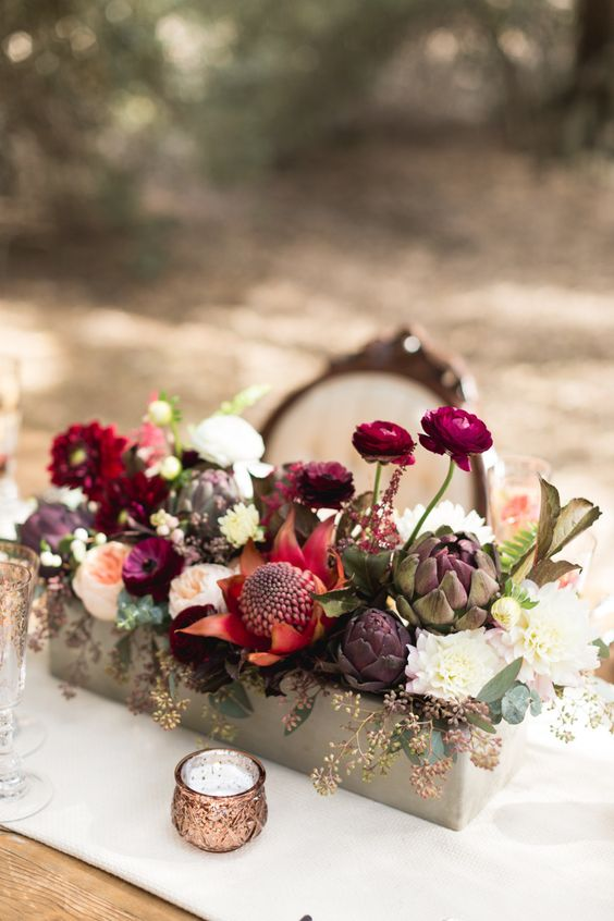 a large concrete box filled with white, blush, plum blooms and artichokes