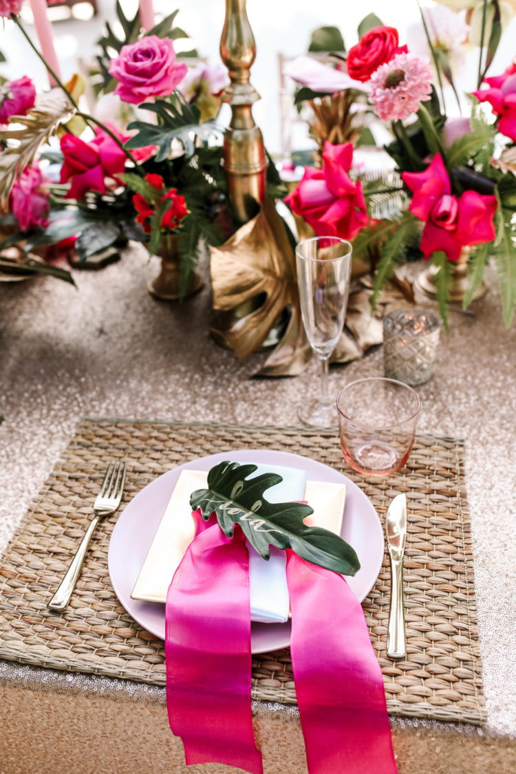 A jute place setting, palm leaves and pink ribbons for a bold and chic look
