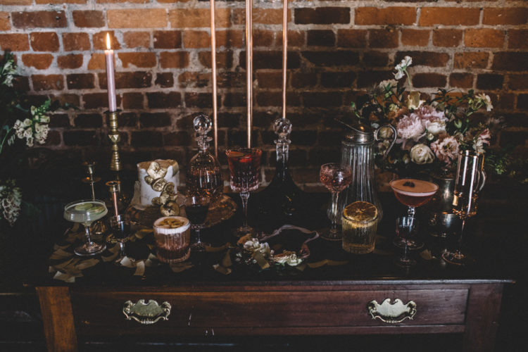 A refined cocktail bar with dusty pink candles and desserts