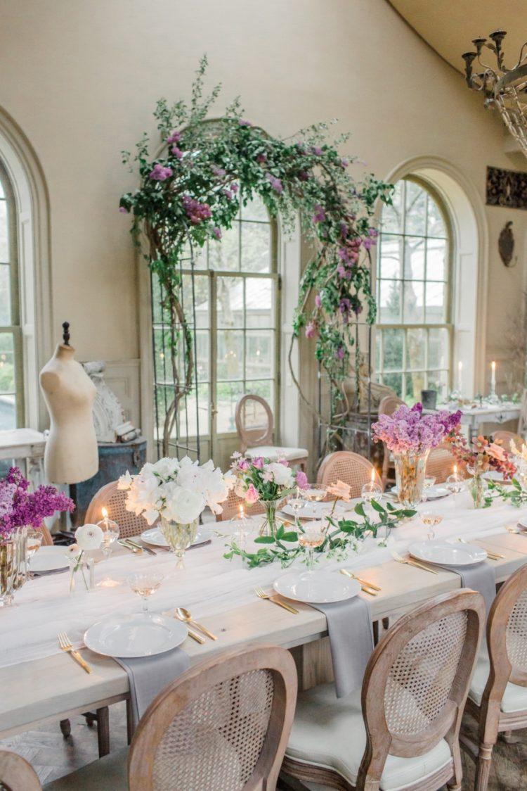 Hochzeit Tisch war dekoriert im französischen Stil, mit weißen und lila Blüten, eine luftige Tischläufer und Neutrale Servietten