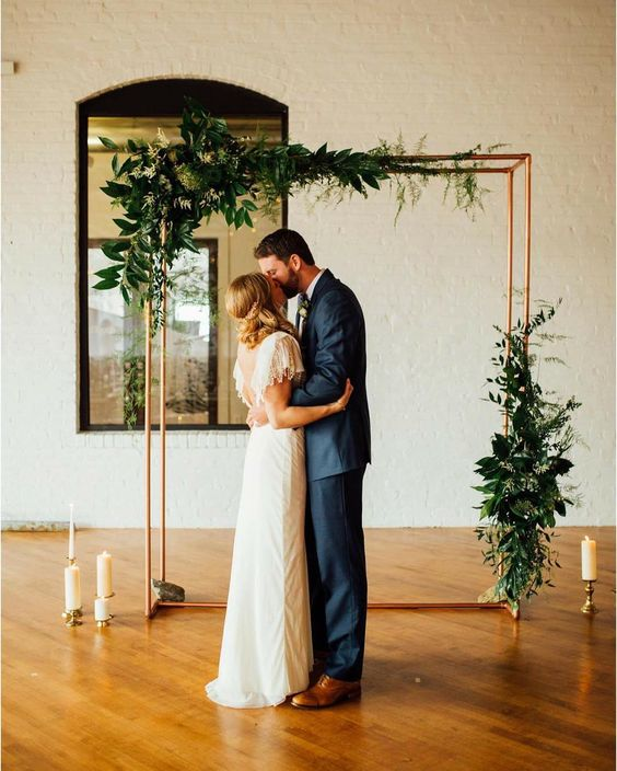 a copper wedding arch with lush greenery and candles all around