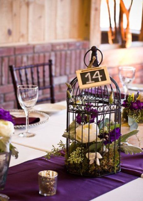 a dark birdcage with purple and white flowers and moss for a bold wedding, a chalkboard table number