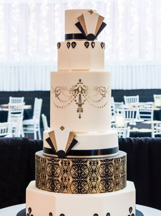 a large round wedding cake with gold and black lace decor, gold and black geo decorations and ribbons