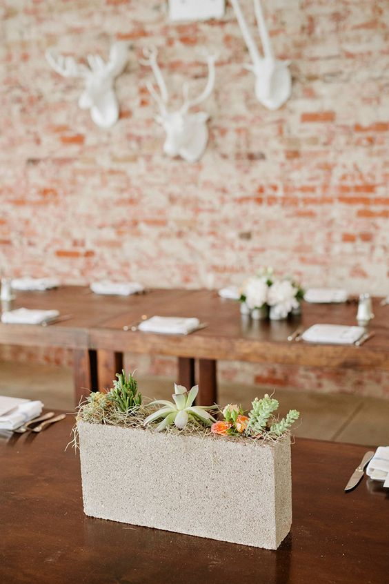 a narrow and tall concrete block wedding centerpiece filled with succulents