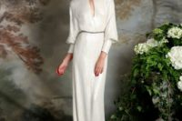 08 an ivory wedding dress with long sleeves, a loop cutout and beading on the neckline and waist