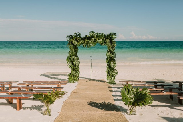 The ceremony space was on the beach, it was a tropical leaf arch and a backdrop of the ocean