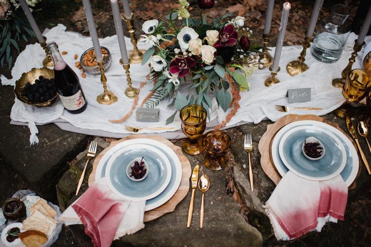 Picknick-tablescape fertig war mit blauen Geschirr, ombre rosa Servietten, Grau, Kerzen, Bernstein und gold-details