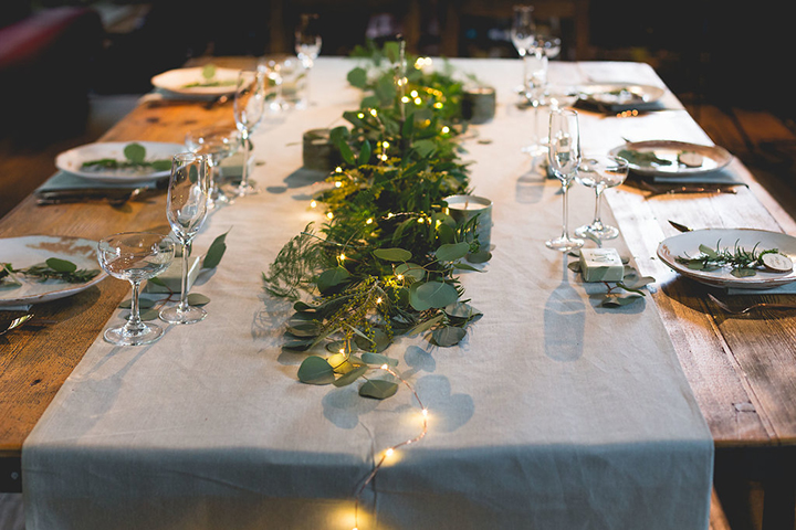 The wedding table setting was done with a neutral fabric runner, greenery, candles and LEDs