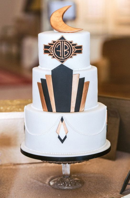 a white cake decorated with black and copper geo decor, a gold moon topper