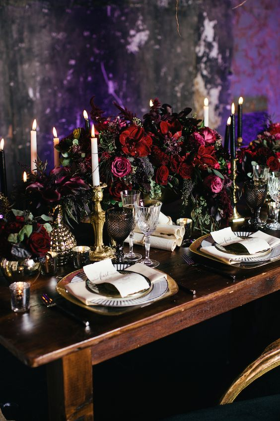 refined wedidng table setting with moody burgundy florals, candles and gilded details