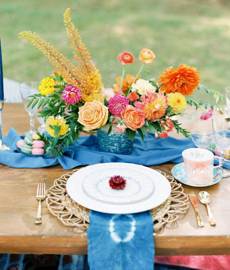 Die tablescape wurde mit einem Fetten blauen Tischläufer, dip-dye-Servietten, wicker-Ladegeräte, ein Glitzernder blauer vase mit auffälligen Blüten