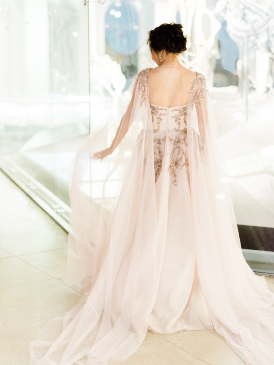 a blush wedding dress with embroidery and beading and a matching cape for a chic look