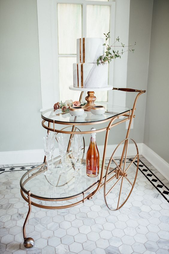 a copper and glass trolley for displaying your wedding cake and alcohol