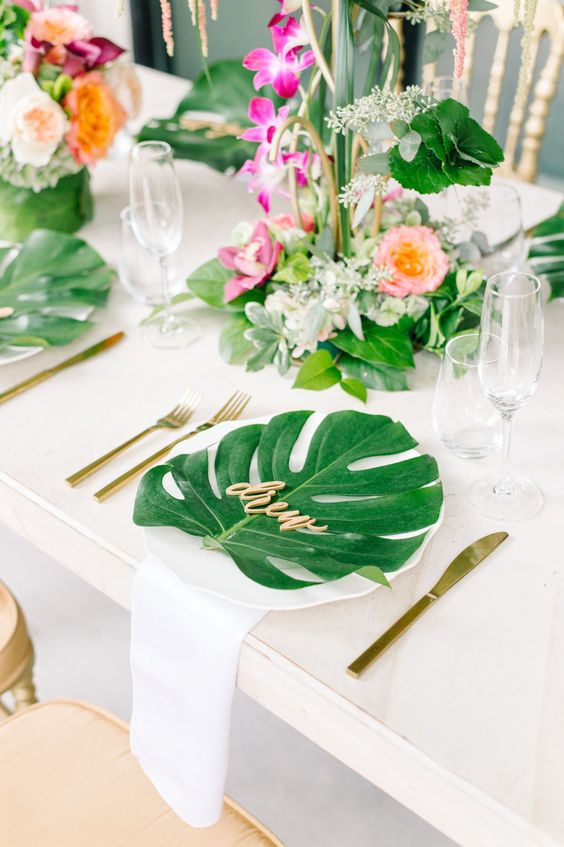 add tropical leaves to each place setting to highlight your wedding scheme