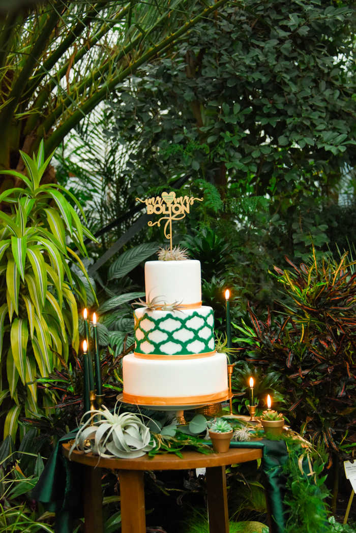 The wedding cake was white, emerald and gold, with a pattern and air plants and a gold topper