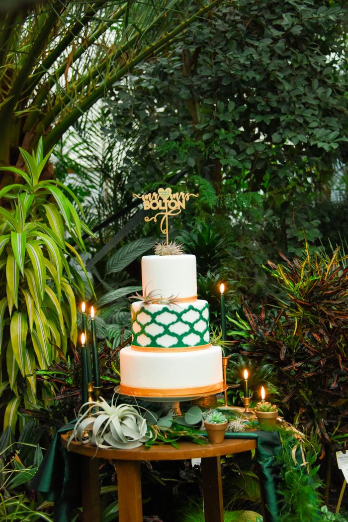 Die Hochzeitstorte war weiss, Smaragd und gold, mit einem Muster und Luft Pflanzen und ein gold topper