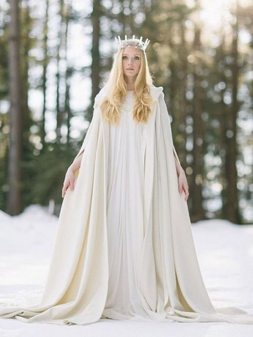 a boho wedding dress paired with a creamy cape provides warmth and comfort for a winter bride