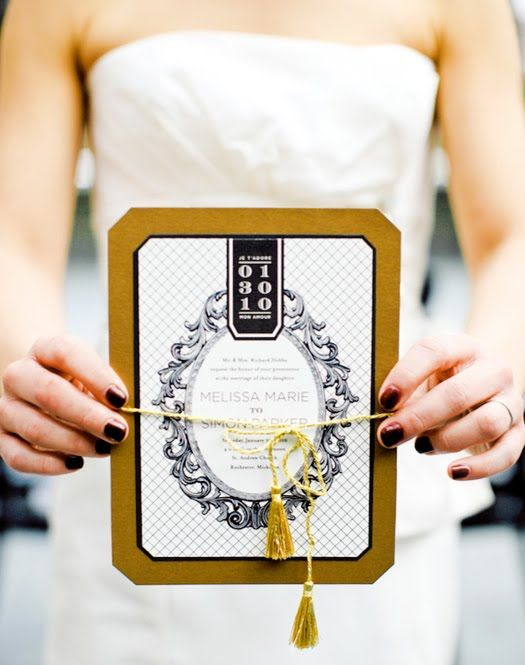 a wedding invitation in black, white and mustard with tassels