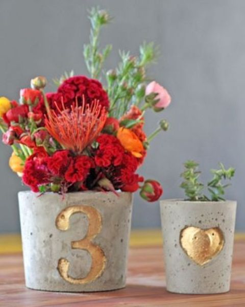 pots with gilded table numbers and a heart and filled with blooms